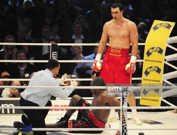 World heavyweight champion Vladimir Klitschko looks on as US challenger Hasim Rahman is counted out by the referee during the IBF and WBO heavyweight...