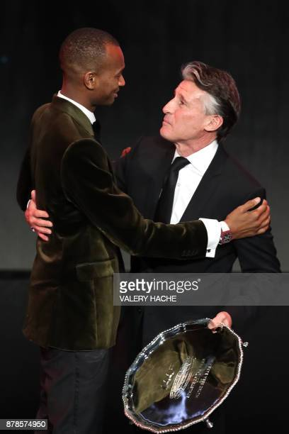 World high jump champion Qatar's Mutaz Essa Barshim receives the trophy of the Male Athlete of the Year 2017 by IAAF President Sebastian Coe during...