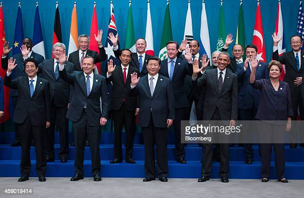 World leaders and delegates wave as they pose for a family photograph at the Group of 20 summit in Brisbane, Australia, on Saturday, Nov. 15, 2014....