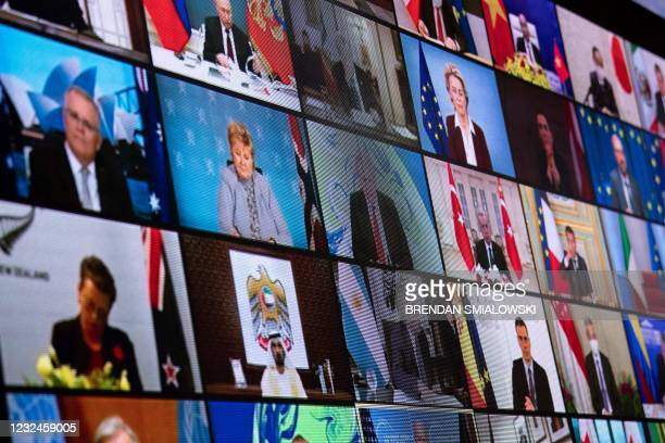 World leaders are seen on a screen during a climate change virtual summit from the East Room of the White House campus April 22 in Washington, DC. -...