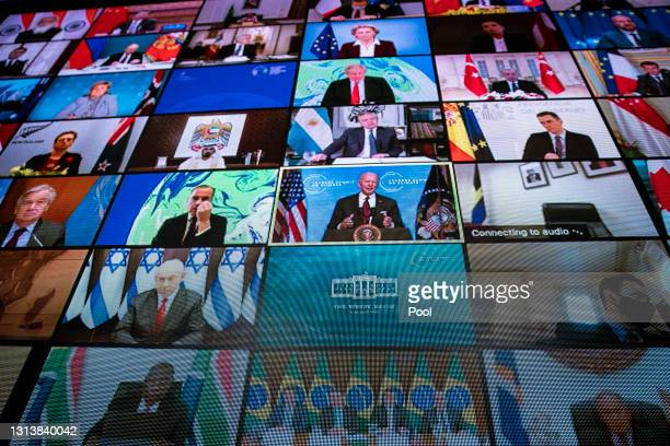 World leaders are seen remotely on a screen as U.S. President Joe Biden delivers remarks during a virtual Leaders Summit on Climate with 40 world...