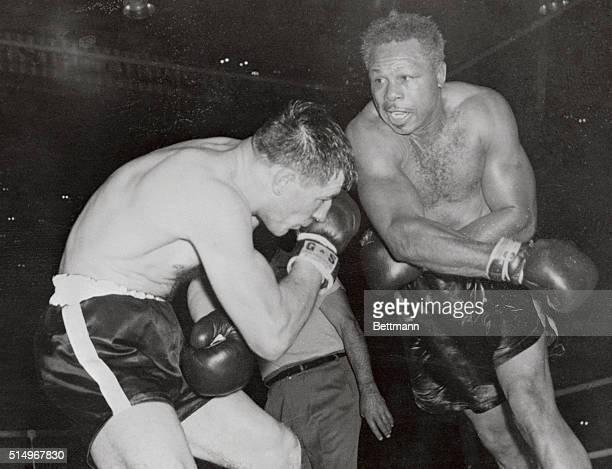 World light heavyweight champion Archie Moore follows through with a right to the head of challenger Yvon Durelle in the ninth round of their...