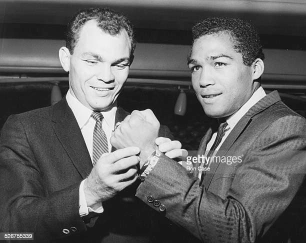 World lightweight boxing champion Carlos Ortiz inspecting the fist of world featherweight boxing champion Sugar Ramos at a luncheon at Isow's...