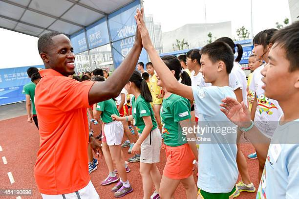World Long Jump champion Dwight Phillips of United States highfives with a boy during the IAAF Kids Athletics Program at Yanshan Road on August 26...