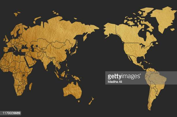 a world map in premium brass | gold | golden | copper color over black background - mapa mundi fotografías e imágenes de stock