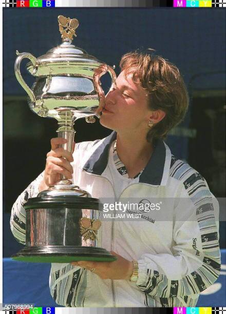 World No 2 Martina Hingis of Switzerland kisses her trophy after defeating Mary Pierce of France in the singles final of the Australian Open tennis...