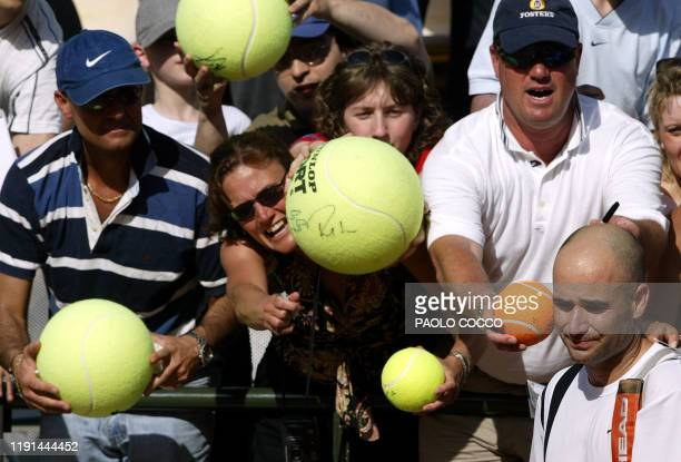 World number one and defending champion US Andre Agassi leaves the court after his memorable defeat by Spanish David Ferrer as his fans ask for...