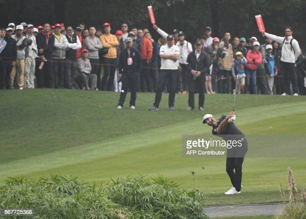 World number one Dustin Johnson of the US chips a shot to the green during the final round of the 975 million USD WGCHSBC Champions at the Sheshan...