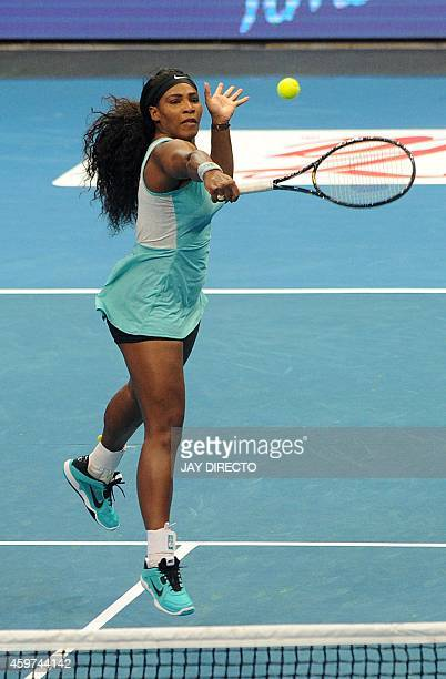 World number one tennis player Serena Williams of the Singapore Slammers strikes the ball in her women's singles match against Kirsten Flipkens of...