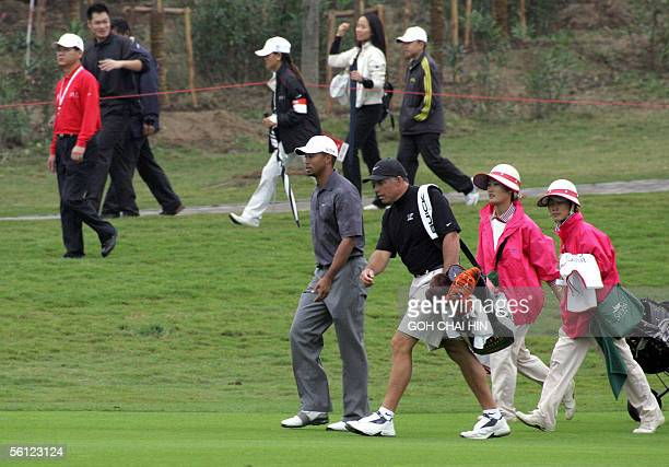 World number one Tiger Woods and his caddy make their way down a fairway during a practice round at the fivemilliondollar HSBC Champions tournament...
