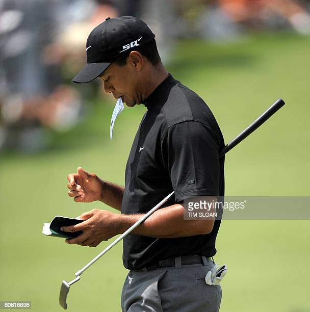 World number one Tiger Woods of the US acknowledges the gallery checks his notes after putting on the second hole during the second round of the US...