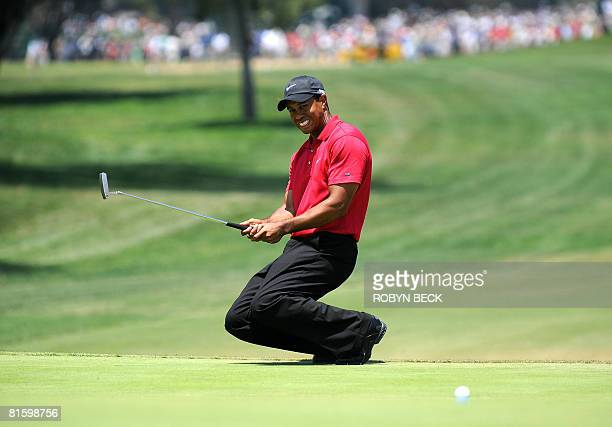World number one Tiger Woods of the US drops to his knees after missing a birdie putt on a sudden death hole following an 18hole playoff round for...