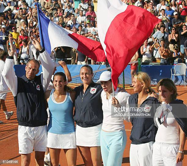 World number three Amelie Mauresmo of France celebrates with her coach Guy Forget and her teammates Mary Pierce Nathalie Dechy Tatiana Golovin and...