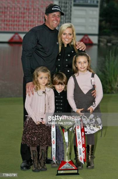World number two Phil Mickelson from the US poses with his wife Amy and children Sophia Isabel Evan and Amanda Brynn with the trophy after winning...