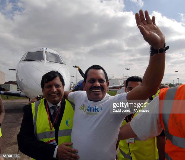 World record holder 57-year-old Manjit Singh from Leicester celebrates his success with friends after pulling an eight-ton Jetstream 41 with his ears.