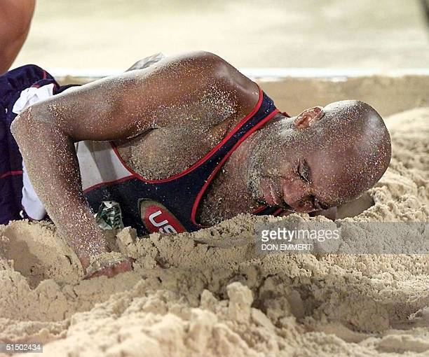 World record holder in the long jump Mike Powell of the US lies in the sand pit 29 July after hurting his leg in his final attempt Teammate Carl...