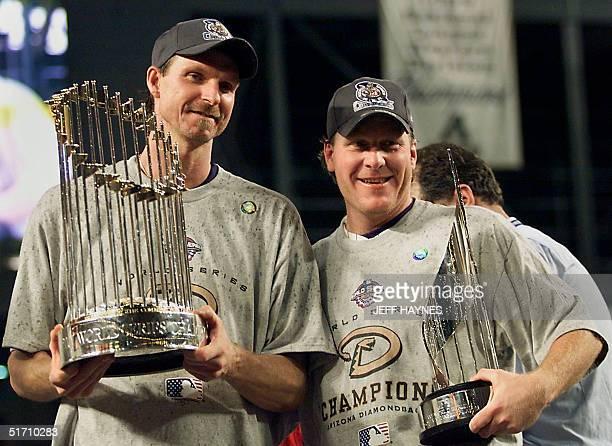 World Series co-MVPs Arizona Diamondbacks pitchers Randy Johnson and Curt Schilling hold the World Series winner's trophy and the MVP trophy during...