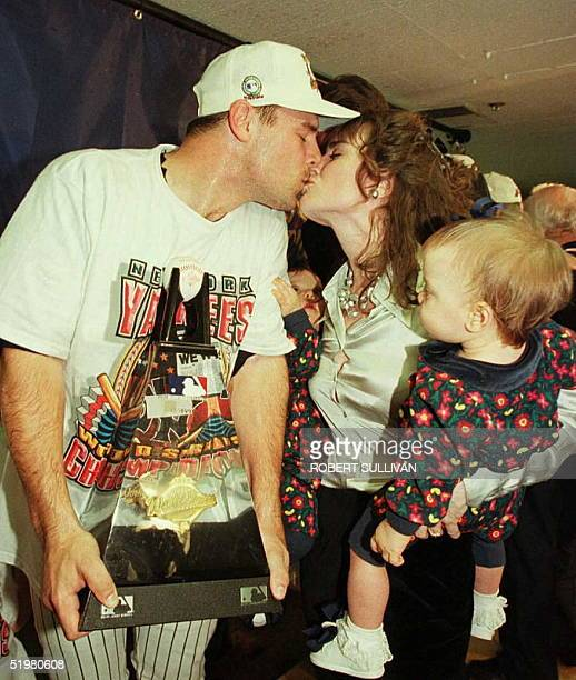 World Series Most Valuable Player relief pitcher John Wetteland of the New York Yankees gets a kiss from his wife Michelle while holding the MVP...