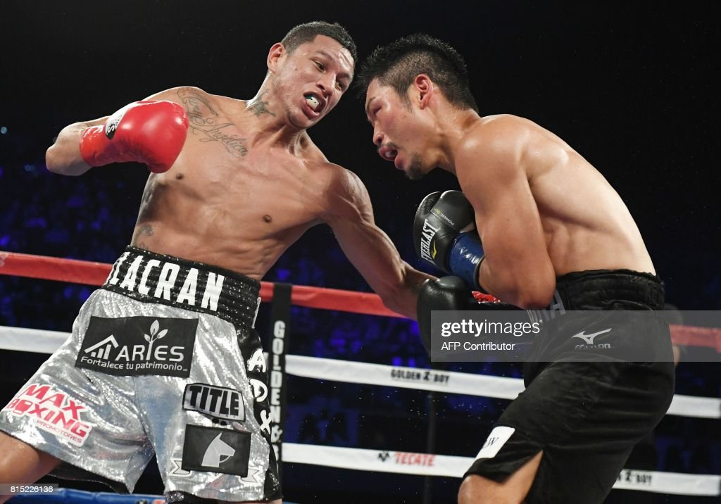 WBC World Super Featherweight champion Miguel Berchelt (L) of Mexico and Japan's Takashi Miura (R) battle in 12th and final round of their title fight, July 15, 2017 at The Forum in Inglewood, California. Berchelt defeated Miura by unanimous decision. / AFP PHOTO / Robyn Beck