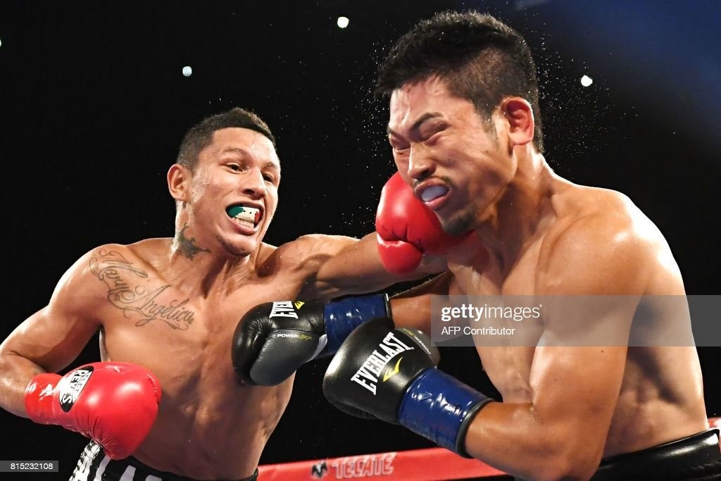 WBC World Super Featherweight champion Miguel Berchelt (L) of Mexico connects with a left against Takashi Miura of Japan in round three of their title fight, July 15, 2017 at The Forum in Inglewood, California. / AFP PHOTO / Robyn Beck