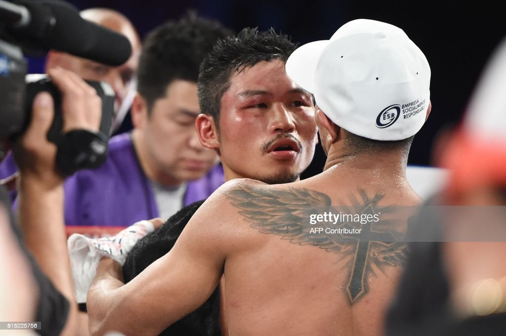 WBC World Super Featherweight champion Miguel Berchelt (R) of Mexico embraces Japan's Takashi Miura after Berchelt defeated Miura in their title fight, July 15, 2017 at The Forum in Inglewood, California. / AFP PHOTO / Robyn Beck