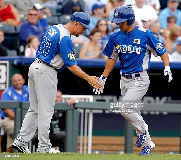World Team third base coach Darren Bush congratulated World Team center fielder Jae-Hoon Ha as he headed toward home plate to score in the second...