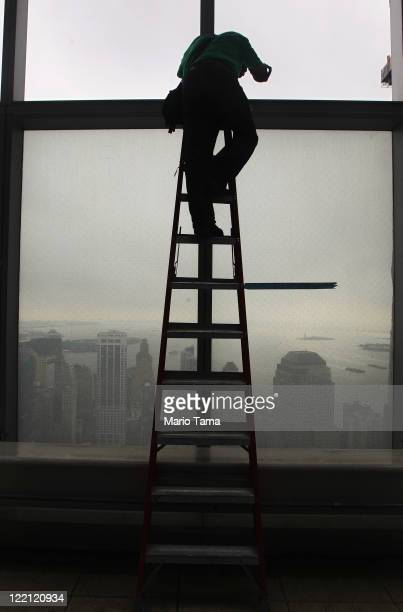 World Trade Center photographer Joe Woolhead takes a photo from a ladder perched on the 53rd floor of 7 World Trade Center as construction continues...