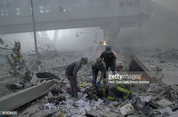 World Trade Center Terrorist Attack-Emergency workers tend to an injured firefighter amidst the rubble in the aftermath of a terrorist attack on the...