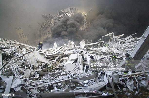 World Trade Center Terrorist Attack-Firefighters look for survivors in the rubble of the World Trade Center after it was struck by a commercial...