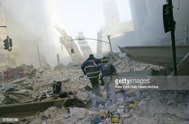 World Trade Center Terrorist Attack-Firefighters walk through the rubble of the World Trade Center after it was struck by a commercial airliner in a...