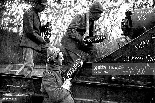 Italian artillery gunners at Easter 1916. Munition shells have East messages written on them . Guns stationed in the Italian Alps intended for...