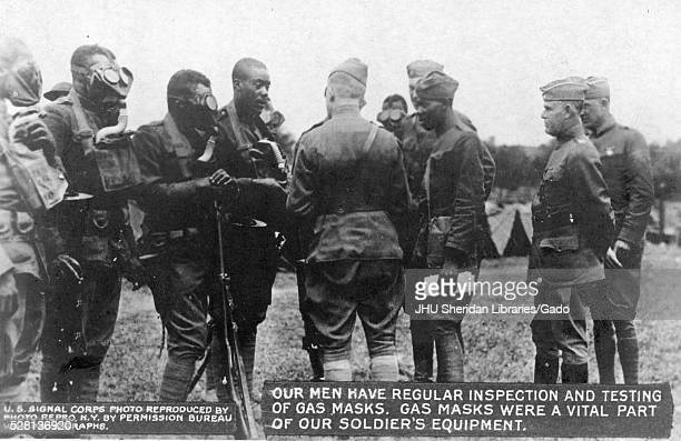 World War 1 US Signal Corps members performing regular inspection and testing of gas masks African American soldiers standing around higher ranked...