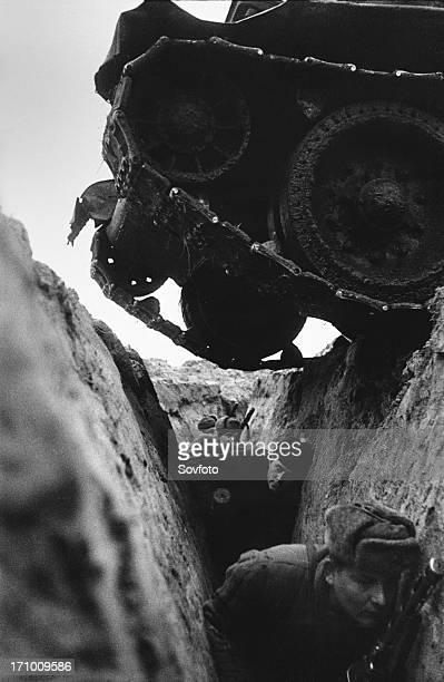 World war 2 battle of kursk soviet t34 tank driving over a trench with red army soldiers 1943