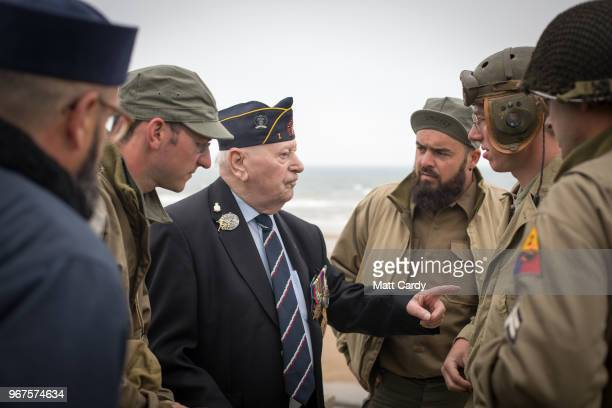 World War 2 reenactors talk with Normandy veterans attending a wreath laying ceremony at the Tactical Air Force Memorial besides Omaha Beach at...