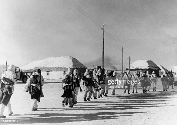 World War - Eastern Front: German combat patrol marching through a village - - Photographer: Presse-Illustrationen Heinrich Hoffmann- Published by:...