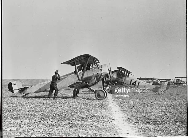 World War I airplane being warmed up on flying field in France.