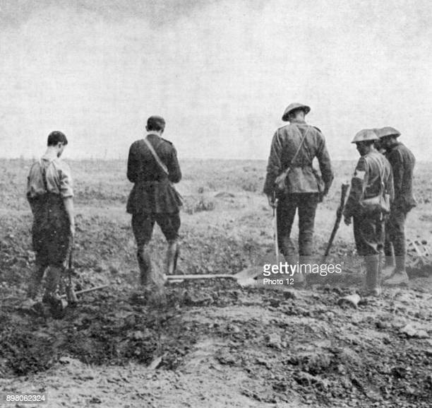 World War I Army chaplain conducting burial service in the field while burial party stand paying their respects Photo12/UIG via Getty Images