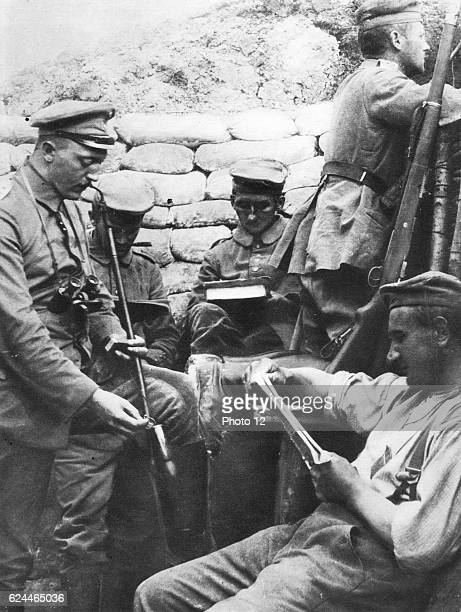 World War I, German soldiers reading, writing and smoking in the trenches during a lull in hostilities.