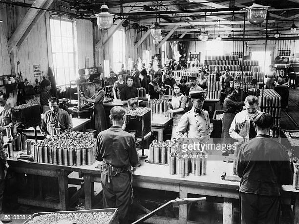 workers insert lead bullets into shrapnels in a staterun ammunition factory undated around 1916/1917