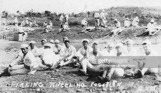 US World War I soldiers sitting on the ground segregated by race facing camera with smiling expressions background consisting of soldiers practicing...