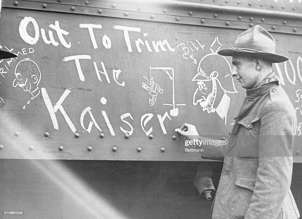 U.S. soldier chalks up ambition of AEF on outside of railroad car. undated photograph.