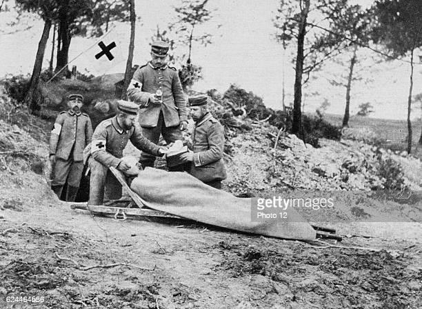 Wounded German soldier on a stretcher being treated behind the trenches by a medical team displaying the symbol of the Red Cross
