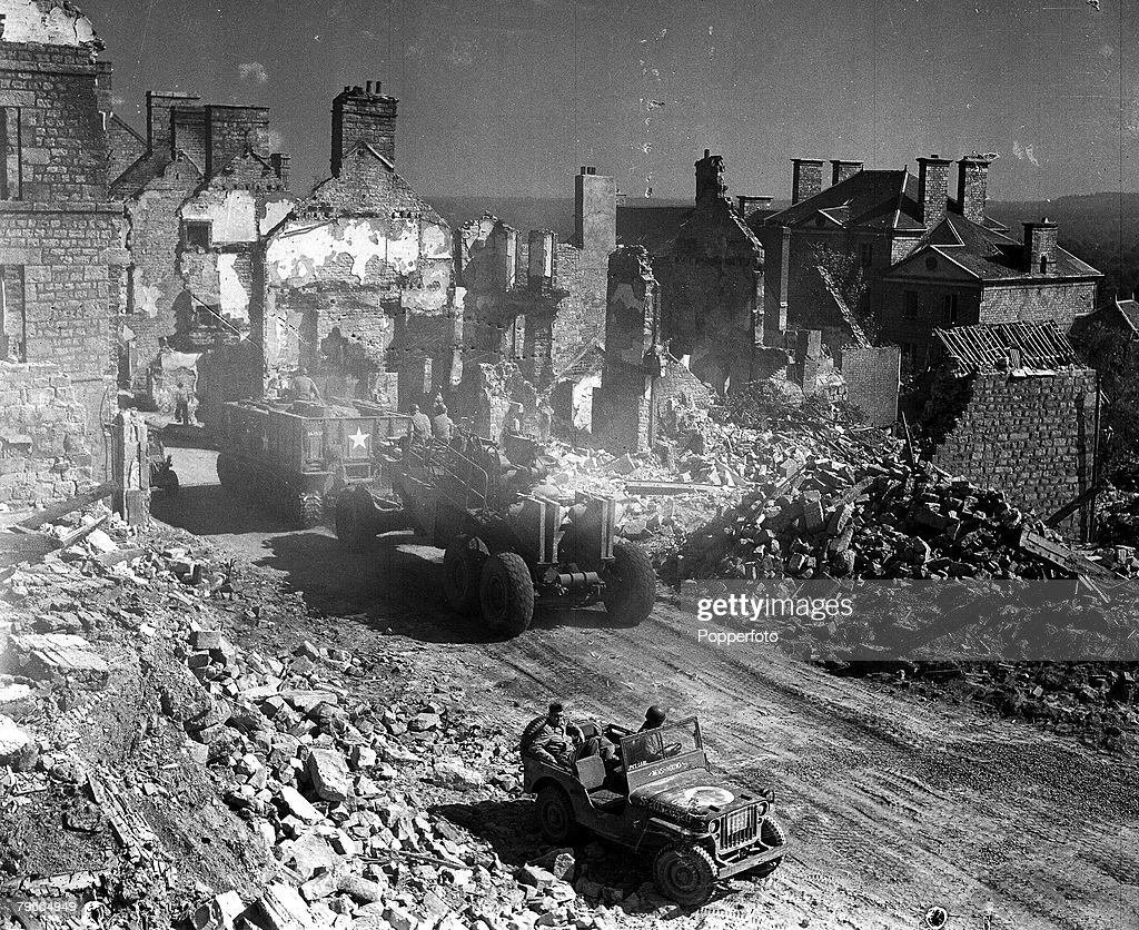World War II, 18th August 1944, American troops pass through a ruined French town during the second World War : News Photo