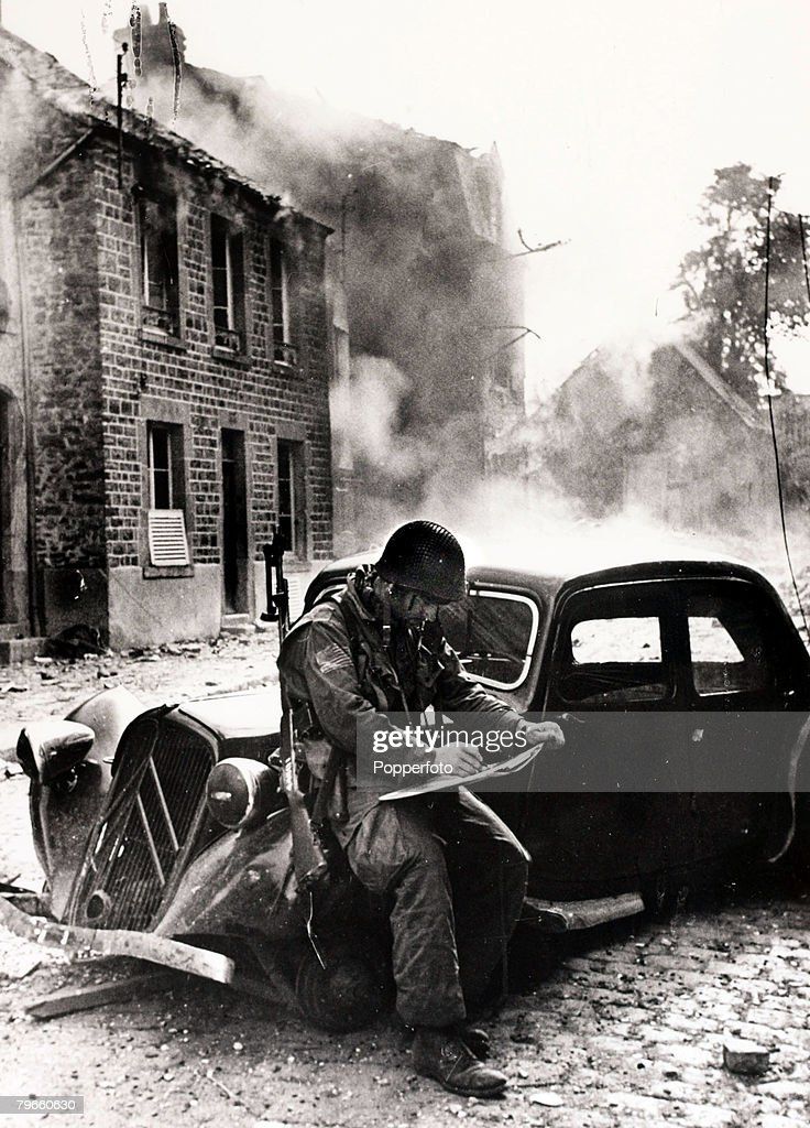 World War II, 22nd June 1944, An American officer pictured in a war-torn street after the D-Day landings in Normandy, France, during the Second World War