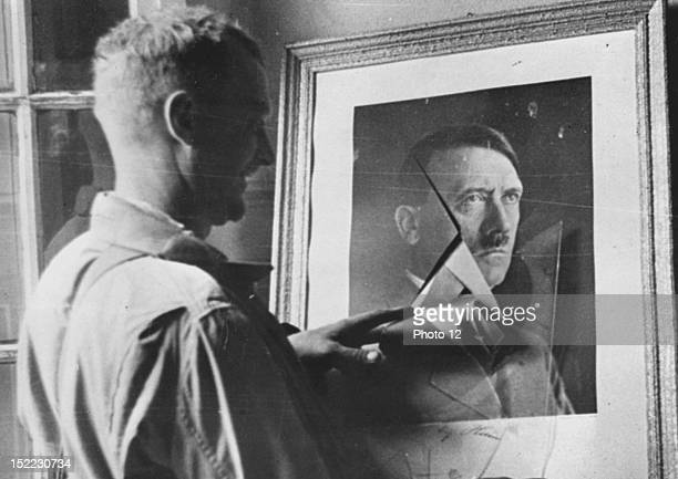 World War II A GI looking at Hitler's portrait which has been destroyed by German officers Sainte Mere l'Eglise Normandie France Around June 6 1944