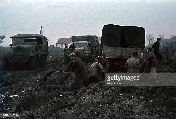 World War II Army Group South German army vehicles on muddy terrain in the Ukraine civilians at roadworks no further details spring 1942 Photographer...