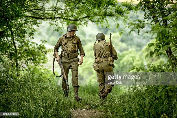world war ii army soldiers march through the forrest - world war ii stock pictures, royalty-free photos & images