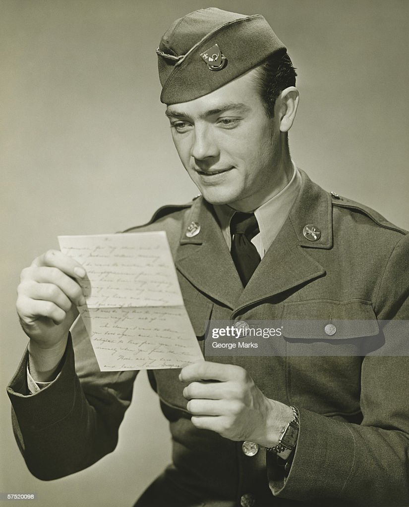 World War II Army solider reading letter in studio, (B&W), portrait : Stock Photo