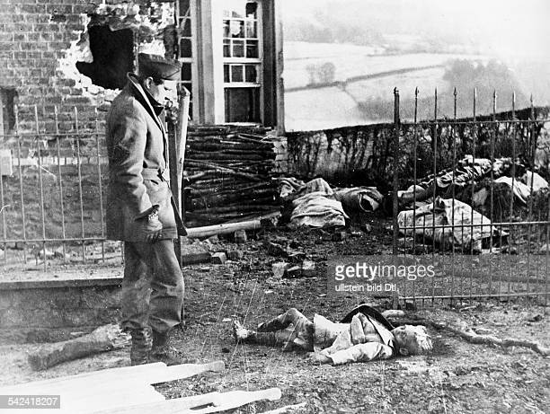 World War II Battle of the Bulge After the recapture of Stavelot by the 9th US Army a soldier standing besides the dead body of a child in the...