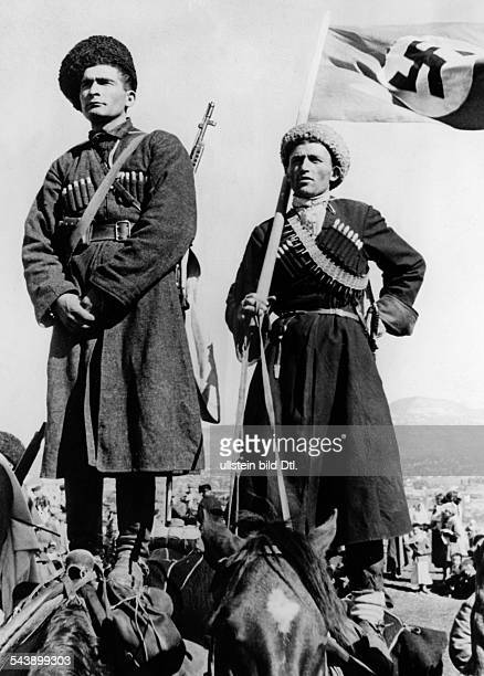 World War II Caucasus region wo volunteers of the Karachay people standing on the backs of their horses and listening to a speech held by a German...
